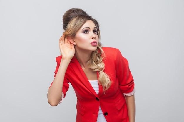 Portrait d'une belle femme d'affaires attentive avec coiffure et maquillage en blazer fantaisie rouge, debout tenant la main sur son oreille et essayant d'écouter. tourné en studio intérieur, isolé sur fond gris.