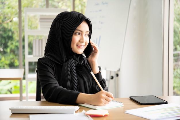 Portrait de belle femme d'affaires musulmane intelligente travaillant au bureau
