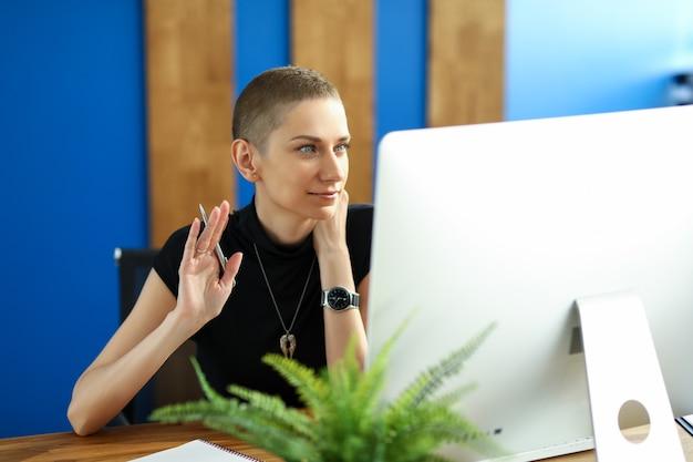 Portrait de belle femme d'affaires parlant sur appel vidéo. ordinateur moderne avec symbole. charmante dame saluant. concept en ligne de réunion de technologie et d'affaires