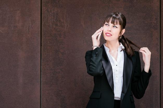Portrait d'une belle femme d'affaires parlant par smartphone sur le chemin du travail