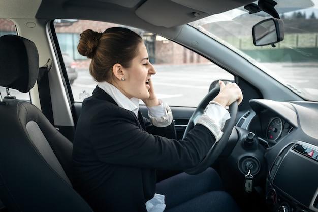 Portrait de belle femme d'affaires parlant par téléphone tout en conduisant une voiture