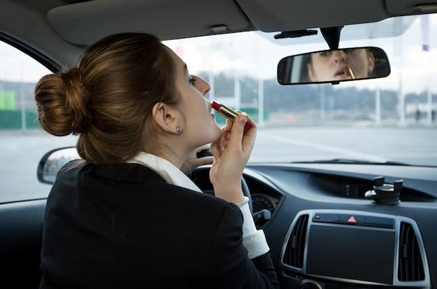 Portrait de belle femme d'affaires regardant dans le miroir de la voiture et appliquant des cosmétiques