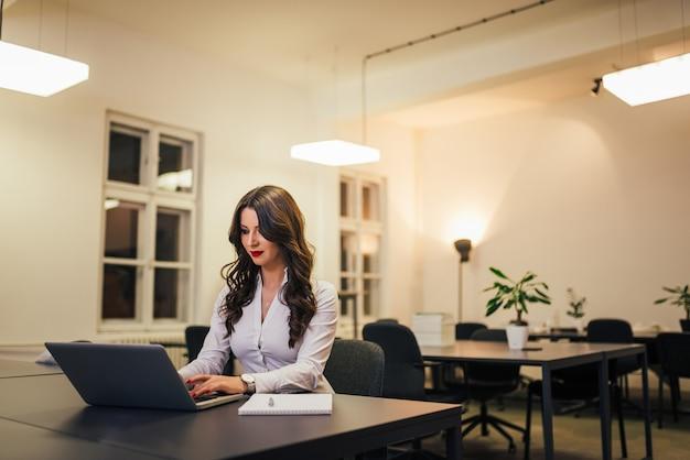 Portrait de belle femme d'affaires avec rouge à lèvres, assis sur le lieu de travail de bureau moderne