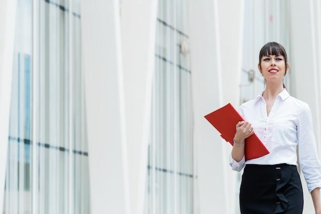 Portrait de belle femme d'affaires tenant un ordinateur portable sur le chemin du travail dans la rue de la ville