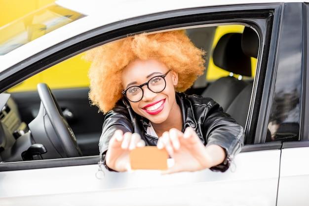 Portrait d'une belle femme africaine souriante en veste de cuir montrant une carte avec un espace vide assis dans la voiture sur fond jaune