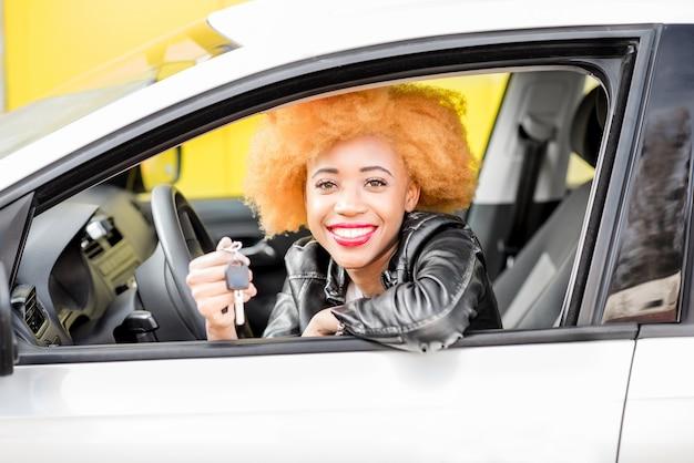 Portrait d'une belle femme africaine souriante en veste de cuir montrant les clés de la voiture sur fond jaune