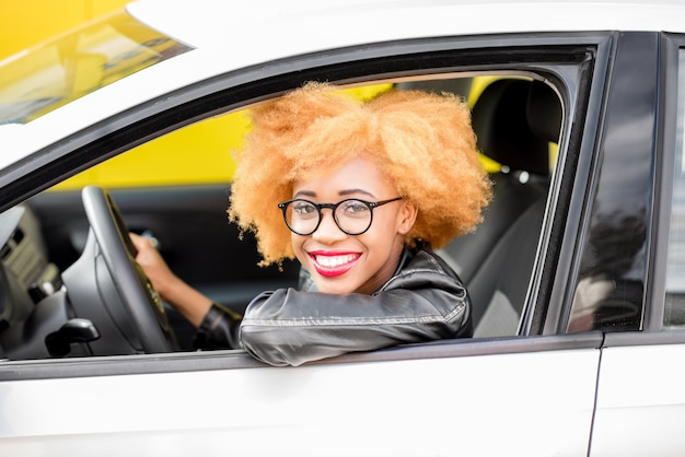 Portrait d'une belle femme africaine en veste de cuir assise dans une voiture sur fond jaune