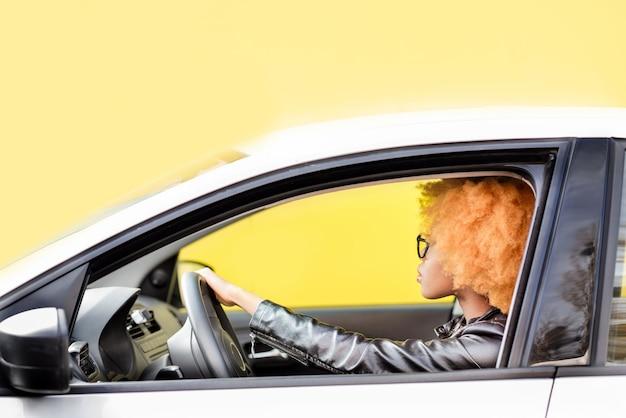 Portrait d'une belle femme africaine en veste de cuir conduisant une voiture sur fond jaune