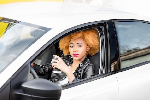 Portrait d'une belle femme africaine en veste de cuir avec une tasse de café assise dans la voiture sur fond jaune
