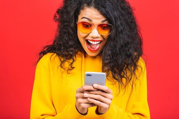Portrait de la belle femme afro-américaine avec des lunettes de soleil à l'aide de téléphone