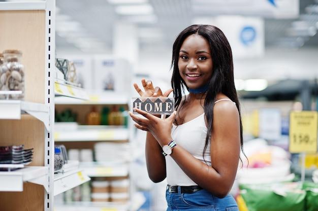 Portrait d'une belle femme afro-américaine tenant une pancarte maison dans le magasin.