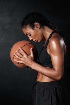 Portrait de la belle femme afro-américaine en tenue de sport tenant le basket-ball isolé sur fond noir