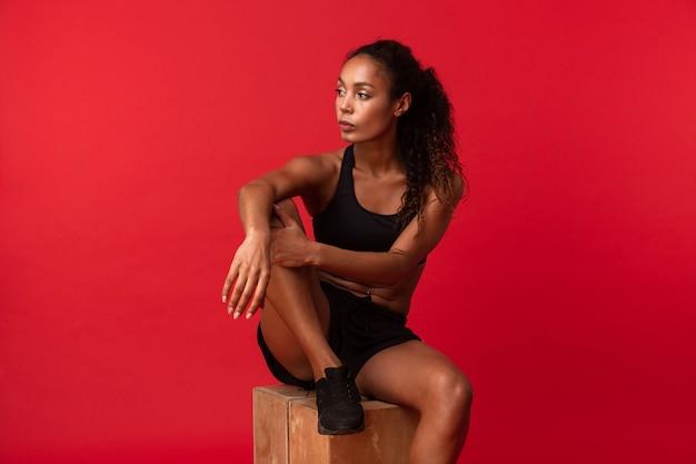 Portrait de la belle femme afro-américaine en vêtements de sport noir assis sur une boîte, isolée sur un mur rouge