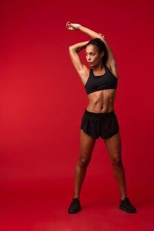 Portrait de la belle femme afro-américaine en vêtements de sport noir qui s'étend de son corps, isolé sur mur rouge