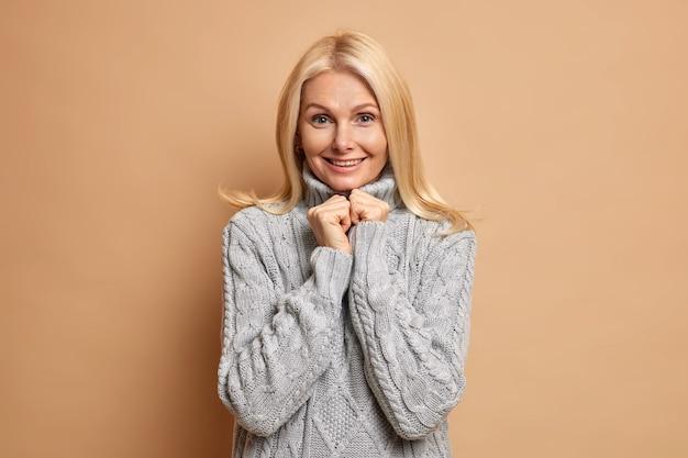 Portrait de belle femme d'âge moyen garde les mains sous le menton a des cheveux blonds naturels maquillage minimal porte un pull gris tricoté chaud regarde calmement.