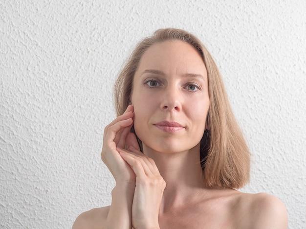 Portrait de la belle femme d'âge moyen touchant son visage sur le mur blanc