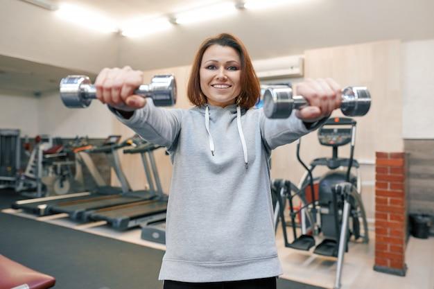 Portrait d'une belle femme d'âge mûr dans une salle de sport.