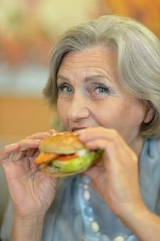 Portrait d'une belle femme âgée mangeant un hamburger