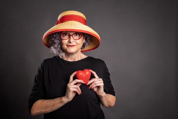 Portrait de belle femme âgée tenant un coeur rouge