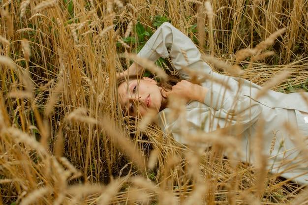 Portrait d'une belle femme agréable qui tient ses cheveux avec sa main, qui est soufflée par le vent. elle se tient sur le toit et sourit.
