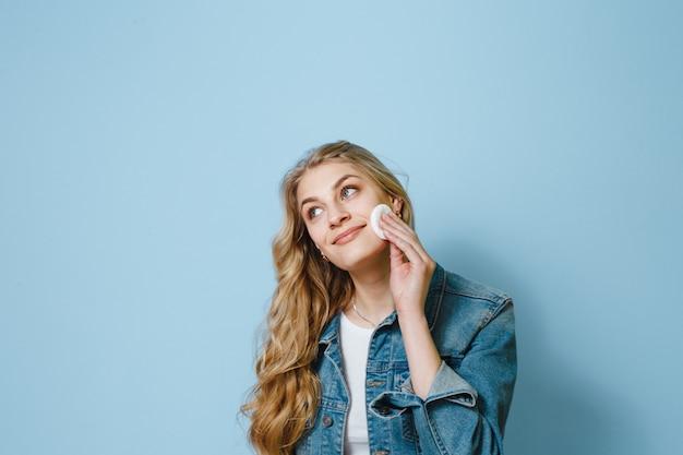 Portrait de belle femme à l'aide d'un coton-tige et pense à quelque chose sur un fond bleu