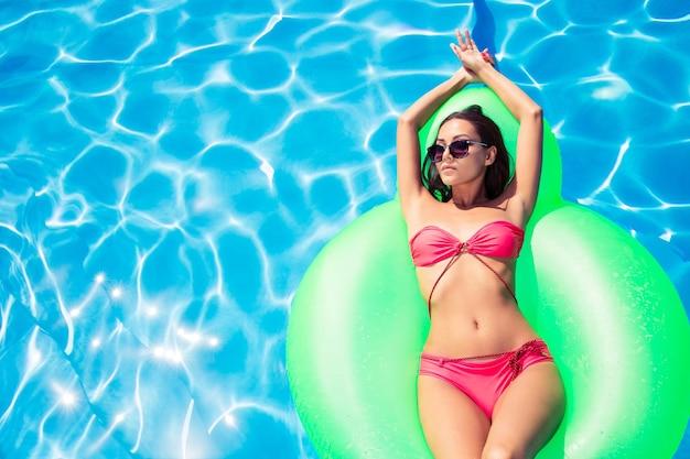 Portrait d'une belle femme allongée sur un matelas pneumatique dans la piscine