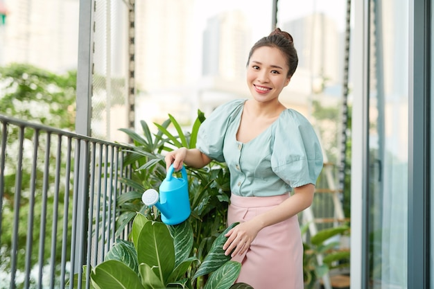 Portrait de la belle femme arrosage des plantes vertes sur le balcon