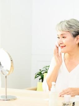 Portrait d'une belle femme asiatique âgée appliquant une houppette au maquillage des joues de cosmétiques.