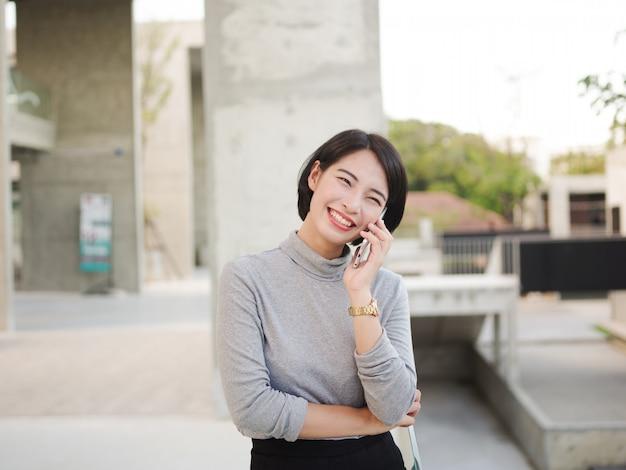 Portrait de la belle femme asiatique à l'aide de téléphone portable dans le look de femme d'affaires jeune