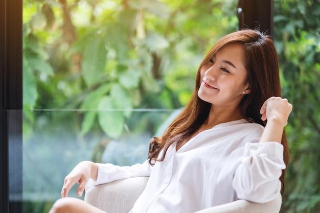 Portrait d'une belle femme asiatique assise sur un fauteuil blanc avec une nature verte