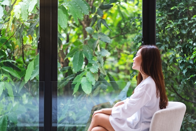 Portrait d'une belle femme asiatique assise et regardant une nature verte à l'extérieur de la fenêtre