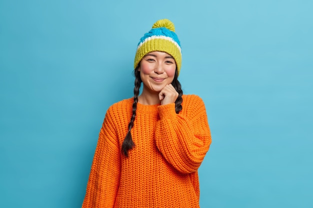 Portrait de belle femme asiatique brune timide avec deux nattes porte pull et chapeau a satisfait l'expression du visage pose en studio contre le mur bleu se promène pendant l'hiver