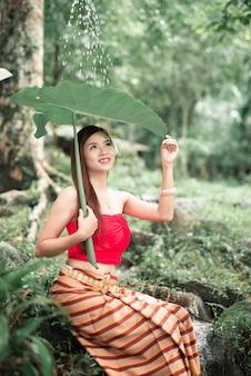 Portrait de la belle femme asiatique à cascade dans la jungle