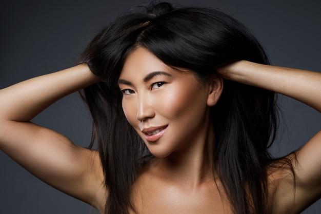 Portrait de la belle femme asiatique avec des cheveux noirs en bonne santé