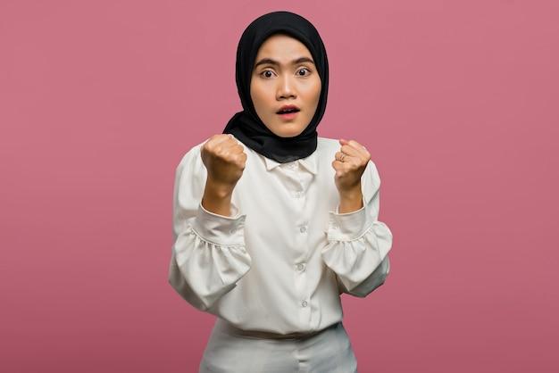 Portrait de la belle femme asiatique choquée et excitée portant une chemise blanche