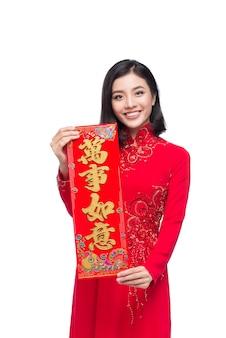 Portrait d'une belle femme asiatique en costume de festival traditionnel ao dai montrant les rouleaux du nouvel an vacances du têt. nouvelle année lunaire. le texte signifie le bonheur et l'enrichissement.