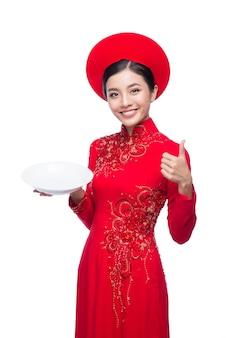 Portrait d'une belle femme asiatique en costume de festival traditionnel ao dai tenant un plat. vacances du têt. nouvelle année lunaire.