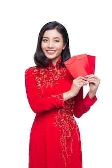 Portrait d'une belle femme asiatique en costume de festival traditionnel ao dai tenant une poche rouge - argent chanceux. vacances du têt. nouvelle année lunaire.