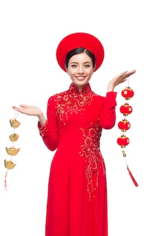 Portrait d'une belle femme asiatique en costume de festival traditionnel ao dai. vacances du têt. nouvelle année lunaire. texte signifie chance et bonheur.