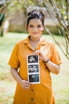 Portrait de belle femme asiatique enceinte tenant des images d'échographie
