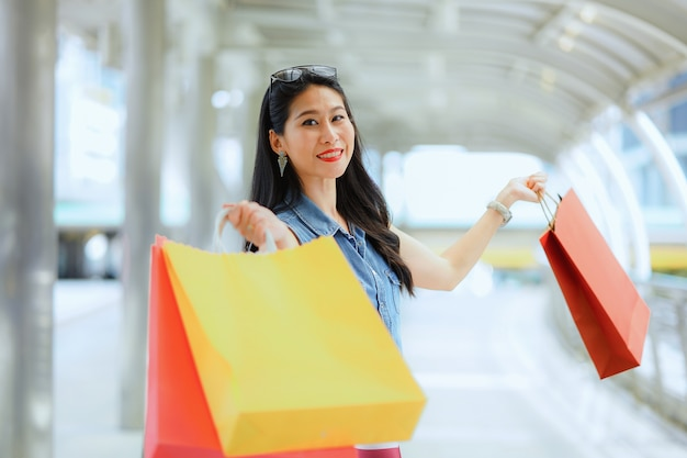 Portrait belle femme asiatique joyeuse main joyeuse tenant avec des sacs à provisions.