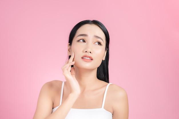 Portrait d'une belle femme asiatique avec un maquillage naturel touchant son visage.