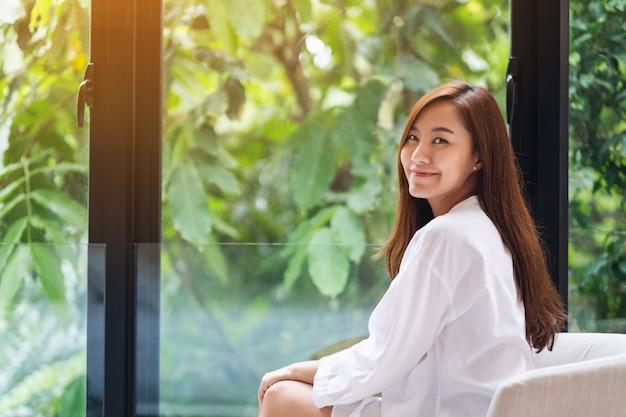 Portrait d'une belle femme asiatique avec une nature verdoyante à l'extérieur de la fenêtre