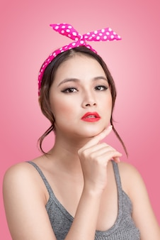 Portrait de belle femme asiatique pin-up avec maquillage et coiffure vintage. isolé sur fond rose
