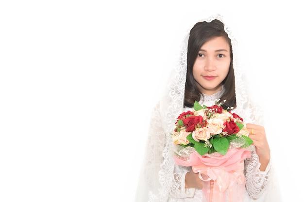 Portrait de la belle femme asiatique portant la robe de mariée sur fond blanc.