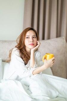 Portrait belle femme asiatique se réveiller et tenant une tasse de café ou une tasse sur le lit le matin