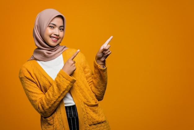 Portrait de la belle femme asiatique souriant et pointant vers un espace vide