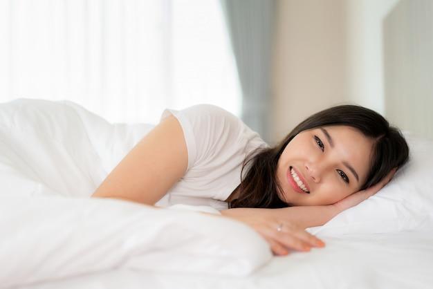 Portrait de la belle femme asiatique avec un sourire attrayant profitez d'un matelas en lin frais et doux dans un appartement moderne de chambre à coucher blanche. mignon asie fille dormir au repos, bonne nuit de sommeil concept.