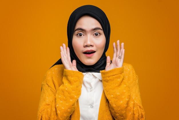 Portrait d'une belle femme asiatique surprise sur fond jaune