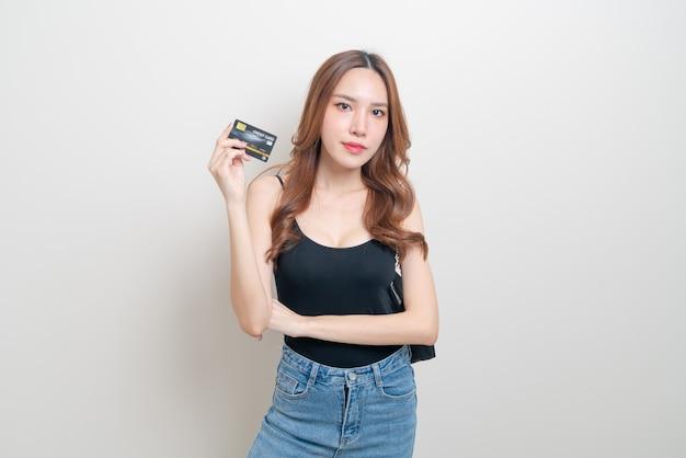 Portrait belle femme asiatique tenant une carte de crédit sur fond blanc